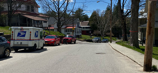 photo showing the pavement and the sidewalk with cars parked along the side of the road, photo taken of Lake Street looking South West at crest of hil