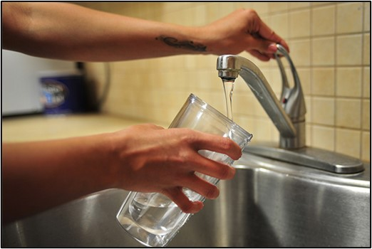 Two hands holding a glass of water and turning on a tap at a sink to fill the glass with water
