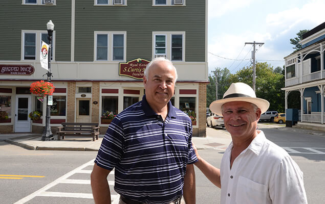 Mayor and property owner pose in front of renovated building