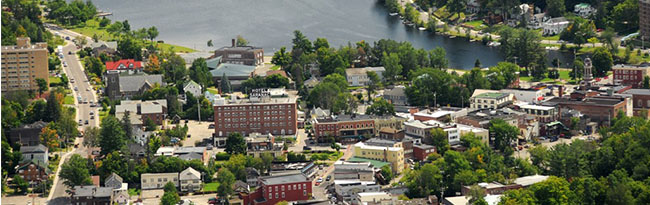 An aerial view of Saranac Lake, NY looking southeast over streets of the Village and the body of wat