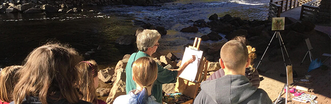 artist painting next to the river