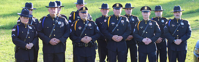 Group photo of Village police officers standing together in uniform on a grassy area.